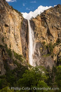 Bridalveil Falls at sunset, with clouds and blue sky in the background. Bridalveil Falls in Yosemite drops 620 feet (188 m) from a hanging valley to the floor of Yosemite Valley, Yosemite National Park, California