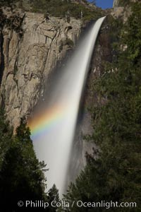 Bridalveil Falls with a rainbow forming in its spray, dropping 620' into Yosemite Valley, displaying peak water flow in spring months from deep snowpack and warm weather melt. Yosemite National Park, California, USA, natural history stock photograph, photo id 27747