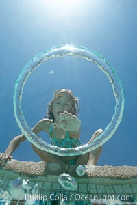 A bubble ring. A young girl reaches out to touch a bubble ring as it ascends through the water toward her