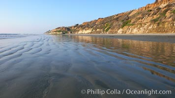 A flat sand beach, sandstone bluffs rise in the background, sunset. Carlsbad, California, USA, natural history stock photograph, photo id 19810