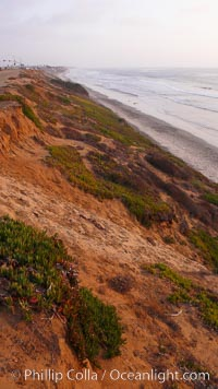 Eroding sandstone bluffs rise above a flat sand beach at sunset, small waves coming ashore, north of South Carlsbad State Beach
