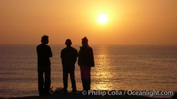 Surf check.  Three guys check the surf from atop a bluff overlooking the waves at the end of the day, at sunset, north of South Carlsbad State Beach