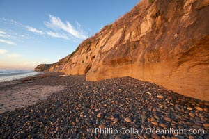Image 22190, Cobblestones piled at the base of seacliffs, sunset.  Beach cliffs made of soft clay continually erode, adding fresh sand and cobble stones to the beach.  The sand will flow away with ocean currents, leading for further erosion of the cliffs. Carlsbad, California, USA, Phillip Colla, all rights reserved worldwide. Keywords: beach, california, carlsbad, coast, cobble, cobble stones, cobblestone, eroded, erosion, ocean, pacific, pebble, rock, sand, sea, sea cliffs, seashore, shore, stone, usa, water, wet.