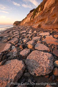 "Remains of the old historic ""Coast Highway 101"", undermined as the bluff upon which it was built eroded away, now broken into pieces of concrete and asphalt blocks and fallen down the sea cliffs, lying on the beach, Carlsbad, California"