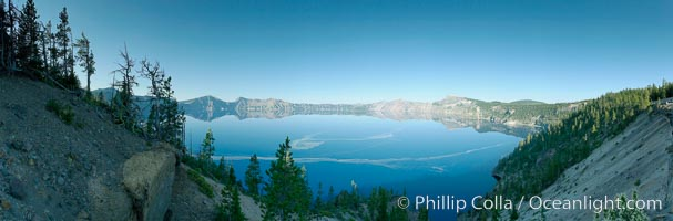 Panorama of Crater Lake, early morning. Crater Lake is the six-mile wide lake inside the collapsed caldera of volcanic Mount Mazama. Crater Lake is the deepest lake in the United States and the seventh-deepest in the world. Its maximum recorded depth is 1996 feet (608m). It lies at an altitude of 6178 feet (1880m). Crater Lake National Park, Oregon, USA, natural history stock photograph, photo id 19116