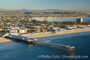 Crystal Pier, 872 feet long and built in 1925, extends out into the Pacific Ocean from the town of Pacific Beach.  Mission Bay and downtown San Diego are seen in the distance