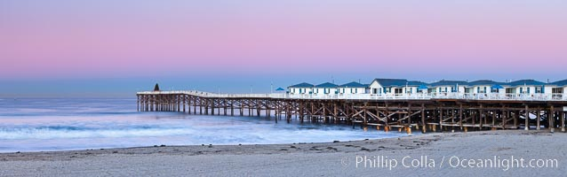 The Crystal Pier and Pacific Ocean at sunrise, dawn, waves blur as they crash upon the sand.  Crystal Pier, 872 feet long and built in 1925, extends out into the Pacific Ocean from the town of Pacific Beach