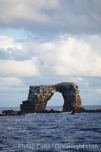 Image 16655, Darwins Arch, a dramatic 50-foot tall natural lava arch, rises above the ocean a short distance offshore of Darwin Island. Darwin Island, Galapagos Islands, Ecuador