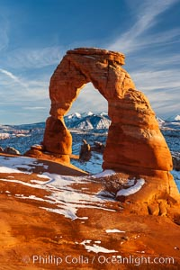 Delicate Arch, dusted with snow, at sunset, with the snow-covered La Sal mountains in the distance.  Delicate Arch stands 45 feet high, with a span of 33 feet, atop of bowl of slickrock sandstone. Delicate Arch, Arches National Park, Utah, USA, natural history stock photograph, photo id 18105