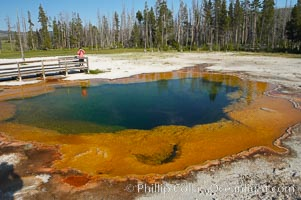 A visitor photographs Emerald Pool, Black Sand Basin, Yellowstone National Park, Wyoming