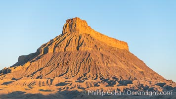 Factory Butte at sunrise. An exceptional example of solitary butte surrounded by dramatically eroded badlands, Factory Butte stands alone on the San Rafael Swell, Hanksville, Utah