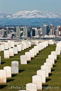 Tombstones at Fort Rosecrans National Cemetery, with downtown San Diego with snow-covered Mt. Laguna in the distance. San Diego, California, USA, natural history stock photograph, photo id 26574