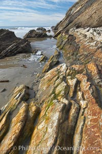 Shale is a fine-grained detrital sedimentary rock formed by the compaction of clay, silt, or mud.  Shale is formed when mud is pressed into rock over millions of years and often breaks into big flat pieces. Here layers of shale emerge from the sand and cliffs at Gaviota State Beach north of Santa Barbara. California, USA, natural history stock photograph, photo id 14894