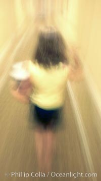 Girl walks down hotel corridor at night, carrying ice bucket, abstract blur time exposure., natural history stock photograph, photo id 20571