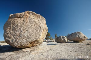 Glacial erratic boulders atop Olmsted Point. Erratics are huge boulders left behind by the passing of glaciers which carved the granite surroundings into their present-day form.  When the glaciers melt, any boulders and other geologic material that it was carrying are left in place, sometimes many miles from their original location, Yosemite National Park, California
