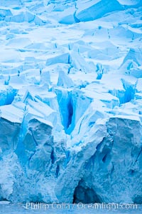 A glacier fractures and cracks, as the leading of a glacier fractures and cracks as it reaches the ocean.  The pieces will float away to become icebergs, Neko Harbor