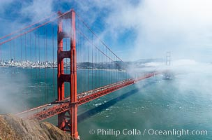 San Franciscos infamous summer fog overtakes the Golden Gate Bridge, viewed from the Marin Headlands with the city of San Francisco visible in the distance. California, USA, natural history stock photograph, photo id 09064