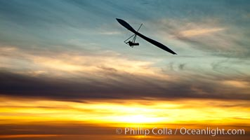 Hang Glider soaring at Torrey Pines Gliderport, sunset, flying over the Pacific Ocean, La Jolla, California