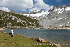 Hiker admires Townsley Lake (10396') and the Cathedral Range in Yosemite's High Sierra, Yosemite National Park, California