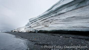Horizontal striations and layers in packed snow, melting and overhanging, seen from the edge of the snowpack, along a rocky beach. Brown Bluff, Antarctic Peninsula, Antarctica, natural history stock photograph, photo id 24871