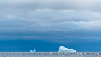 Image 24797, Iceberg, ocean, light and clouds.  Light plays over icebergs and the ocean near Coronation Island. Coronation Island, South Orkney Islands, Southern Ocean, Phillip Colla, all rights reserved worldwide. Keywords: berg, british antarctic territory, cold, coronation island, frozen, ice, ice berg, iceberg, landscape, ocean, oceans, outdoors, outside, scene, scenery, sea, seascape, south orkney islands, south orkneys, southern ocean, united kingdom, view, water.