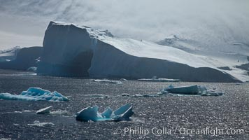 Iceberg and snow-covered coastline, Antarctic Sound. Antarctic Peninsula, Antarctica, natural history stock photograph, photo id 24812