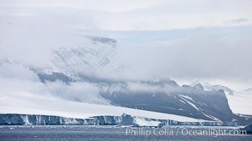 Iceberg and snow-covered coastline, Antarctic Sound. Antarctic Sound, Antarctic Peninsula, Antarctica, natural history stock photograph, photo id 24875