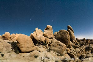 Joshua Tree National Park boulders under a night sky and stars.  Mars is visible in the middle of the image