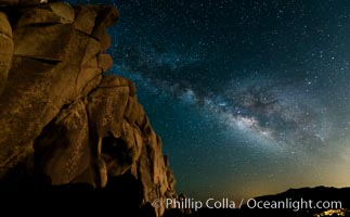 The Milky Way rises above a huge wall of stone, stars fill the night sky and soar over the distant lights of campers. Joshua Tree National Park, California, USA, natural history stock photograph, photo id 27898