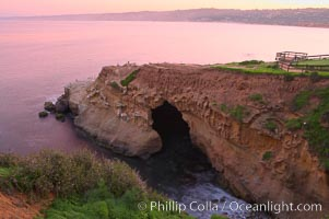 A large natural sea cave lies below a sandstone bluff in La Jolla at sunrise with a pink sky, Black's Beach in the distant