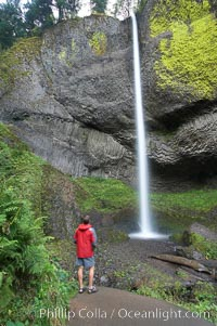 A hiker admires Latourelle Falls, in Guy W. Talbot State Park, drops 249 feet through a lush forest near the Columbia River, Columbia River Gorge National Scenic Area, Oregon