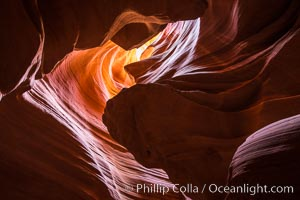 Light Beam in Upper Antelope Slot Canyon.  Thin shafts of light briefly penetrate the convoluted narrows of Upper Antelope Slot Canyon, sending piercing beams through the sandstone maze to the sand floor below, Navajo Tribal Lands, Page, Arizona