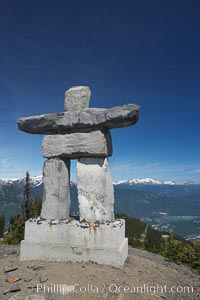 Ilanaaq, the logo of the 2010 Winter Olympics in Vancouver, is formed of stone in the Inukshuk-style of traditional Inuit sculpture.  Located near the Whistler mountain gondola station, overlooking Whistler Village and Green Lake in the distance. Whistler, British Columbia, Canada, natural history stock photograph, photo id 21010