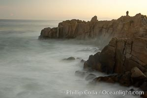 Lovers Point, Pacific Grove.  A couple admires the sunrise atop Lovers Point in Pacific Grove.  Waves breaking over rocks appear as a foggy mist in this time exposure.  Pacific Grove