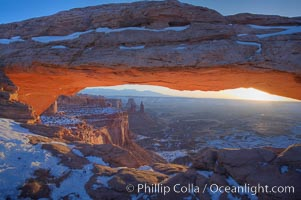 Mesa Arch spans 90 feet and stands at the edge of a mesa precipice thousands of feet above the Colorado River gorge. For a few moments at sunrise the underside of the arch glows dramatically red and orange. Island in the Sky, Canyonlands National Park, Utah, USA, natural history stock photograph, photo id 18039