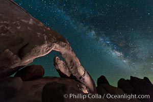 The Milky Way galaxy arcs over Arch Rock on a clear evening in Joshua Tree National Park