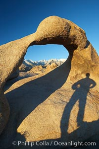 The long shadow of a hiker lies on Mobius Arch, a natural stone arch in the Alabama Hills, Alabama Hills Recreational Area