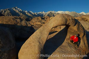 A hiker admires Mobius Arch in early morning golden sunlight, with the snow-covered Sierra Nevada Range and the Alabama Hills seen in the background, Alabama Hills Recreational Area