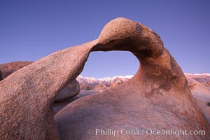 Image 21742, Mobius Arch, with snow covered Mt. Whitney and the Sierra Nevada Range framed within the natural stone arch.  Mt. Whitney is the highest peak in the continental United States. Alabama Hills Recreational Area, California, USA, Phillip Colla, all rights reserved worldwide. Keywords: alabama hills, alabama hills arch, alabama hills recreational area, arch, bureau of land management, california, environment, galen arch, galen's arch, geologic features, geology, landscape, lone pine, lone pine peak, mobius arch, moebius arch, mount whitney, movie road arch, natural arch, natural arches, nature, outdoors, outside, scene, scenery, scenic, sierra nevada, usa.