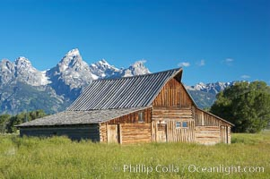 An old barn at Mormon Row is lit by the morning sun with the Teton Range rising in the distance. Mormon Row, Grand Teton National Park, Wyoming, USA, natural history stock photograph, photo id 12997