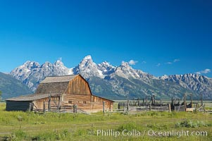 An old barn at Mormon Row is lit by the morning sun with the Teton Range rising in the distance. Grand Teton National Park, Wyoming, USA, natural history stock photograph, photo id 12998