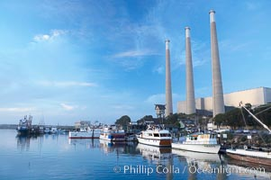 The Morro Bay Power Plant, with its distinctive three stacks, rises above fishing boats in Morro Bay harbor.  Morro Bay