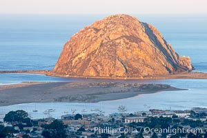 Morro Rock lit at sunrise, rises above Morro Bay which is still in early morning shadow