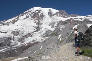 A hiker views the Nisqually Glacier and Mount Rainier from the Skyline Trail, Mount Rainier National Park, Washington