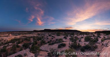 Panorama of Natural Bridges National Monument at sunset. Owachomo Bridge is visible at far left, while Natural Bridges National Monument lies under a beautiful sunset