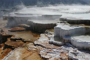 Steam rises from the travertine terraces of New Blue Spring, part of the Mammoth Hot Springs complex, Yellowstone National Park, Wyoming