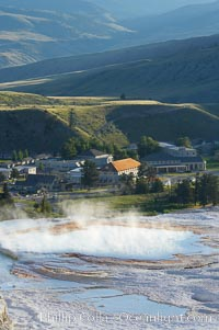 New Blue Spring steams in the cold morning air with Mammoth Hot Springs Inn in the distance, Yellowstone National Park, Wyoming