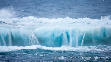 Ocean waves wash over a flat iceberg, carving gulleys into the sides of the iceberg, Scotia Sea