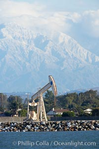 Oil pump, tract homes and snow-covered San Bernardino mountains, viewed from Bolsa Chica State Ecological Reserve, Huntington Beach, California