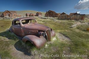Old car lying in dirt field, Fuller Street and Green Street buildings in background. Bodie State Historical Park, California, USA, natural history stock photograph, photo id 23134